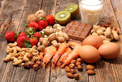 Mesa con fresas, nueces, camarones, huevos, chocolate, leche y kiwi
