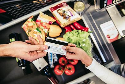 Cliente pasando la tarjeta de credito a la cajera